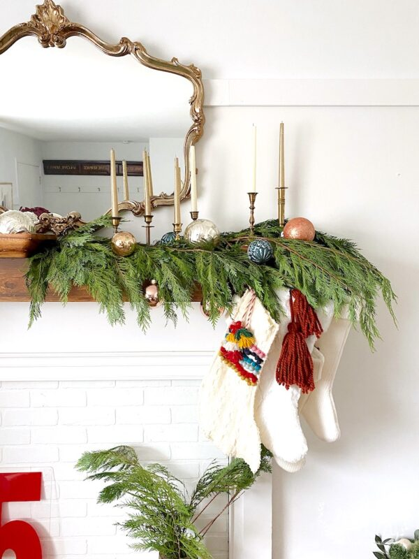 Cedar on mantel with stockings and candle sticks