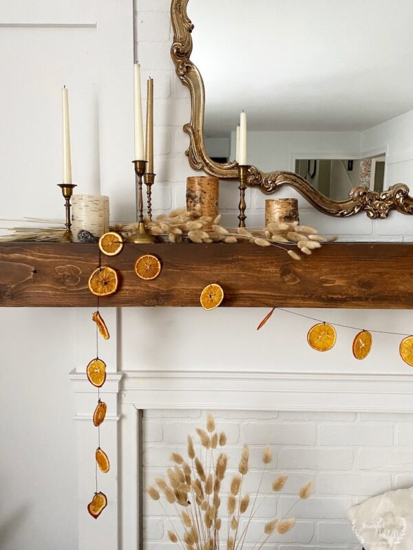 Dried orange slice garland on a box mantel with brass candlesticks