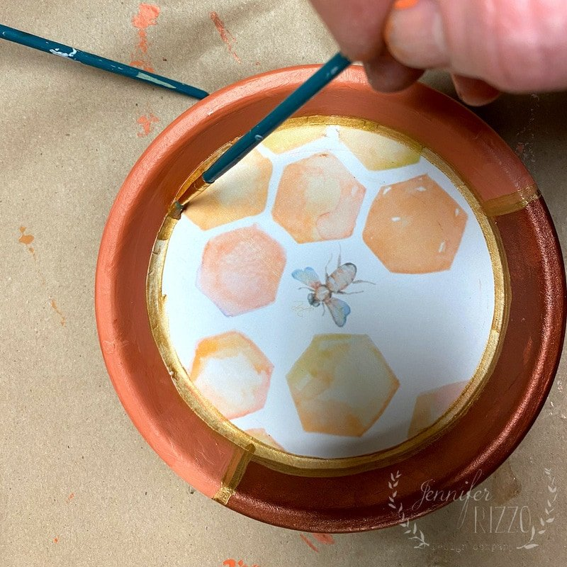 Paint gold accents on dish