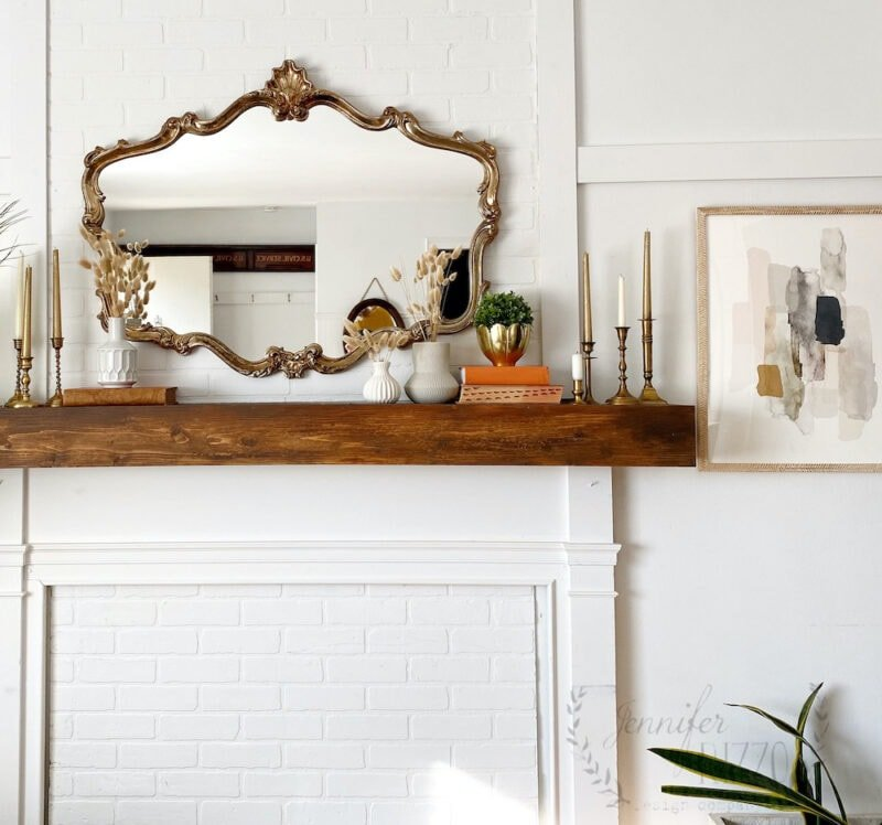 Mantel decor with brass candle sticks, white vases and dried grasses