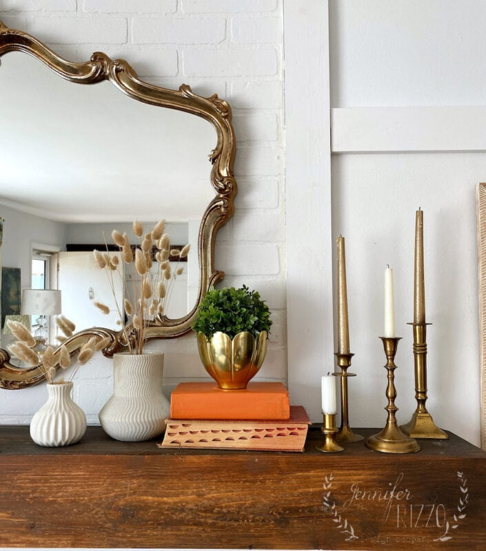 Restyled mantel decor with brass candle sticks, white vases, and bunny tail grass