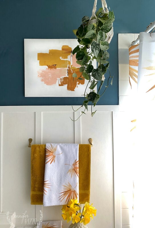 Abstract painting and pothos plant with yellow towels boho bathroom makeover refresh