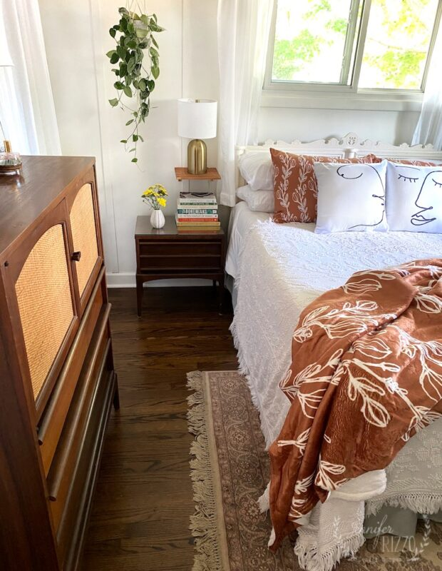 Modern bohemian bedroom makeover with plants and rust colored pillows