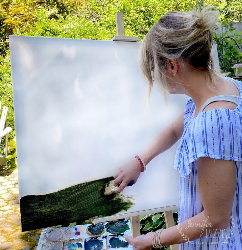 Paint a dark green base color on your canvas to create an abstract landscape