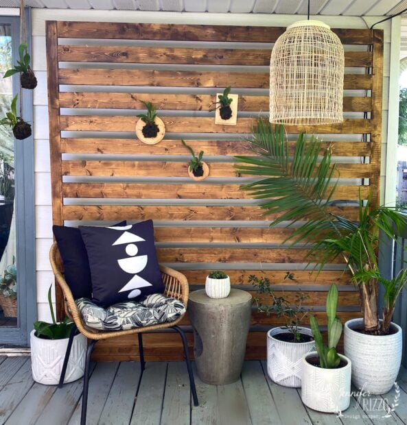 Styled wood panel on back deck with boho hanging light and plants