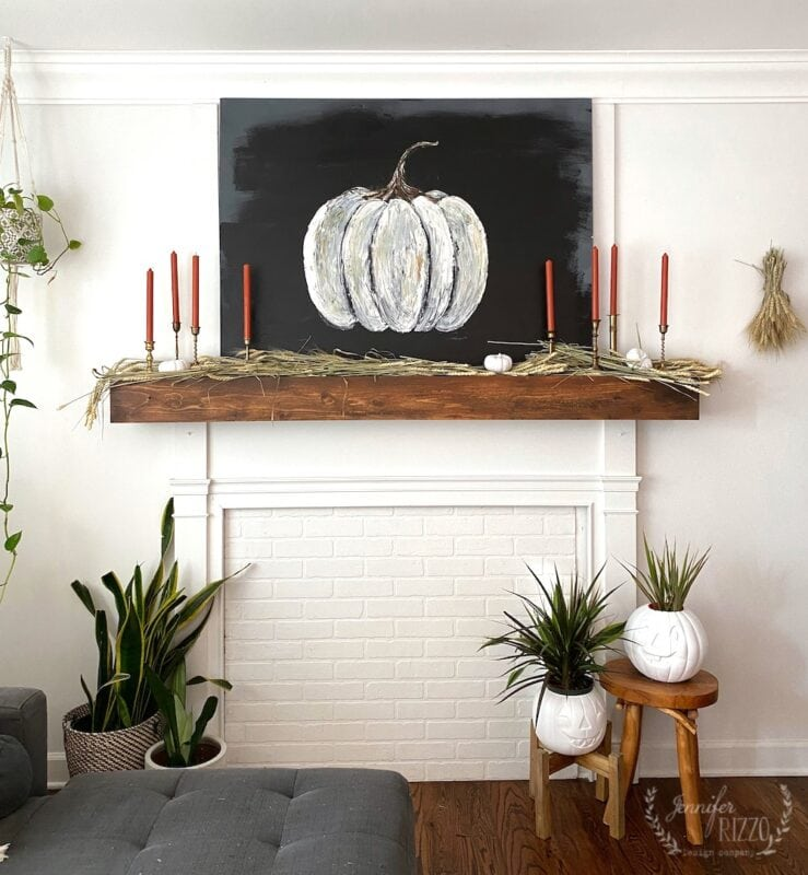 fall mantel with brass cnadles ticks and pumpkins