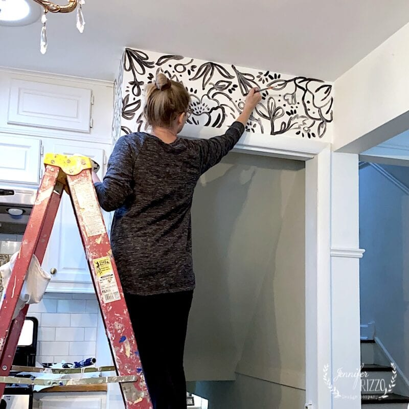 Jennifer Rizzo painting a black and white floral mural