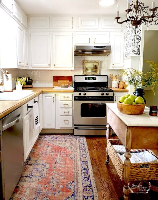 Vintage kilim rug with white cabinets and wood counter tops in kitchen