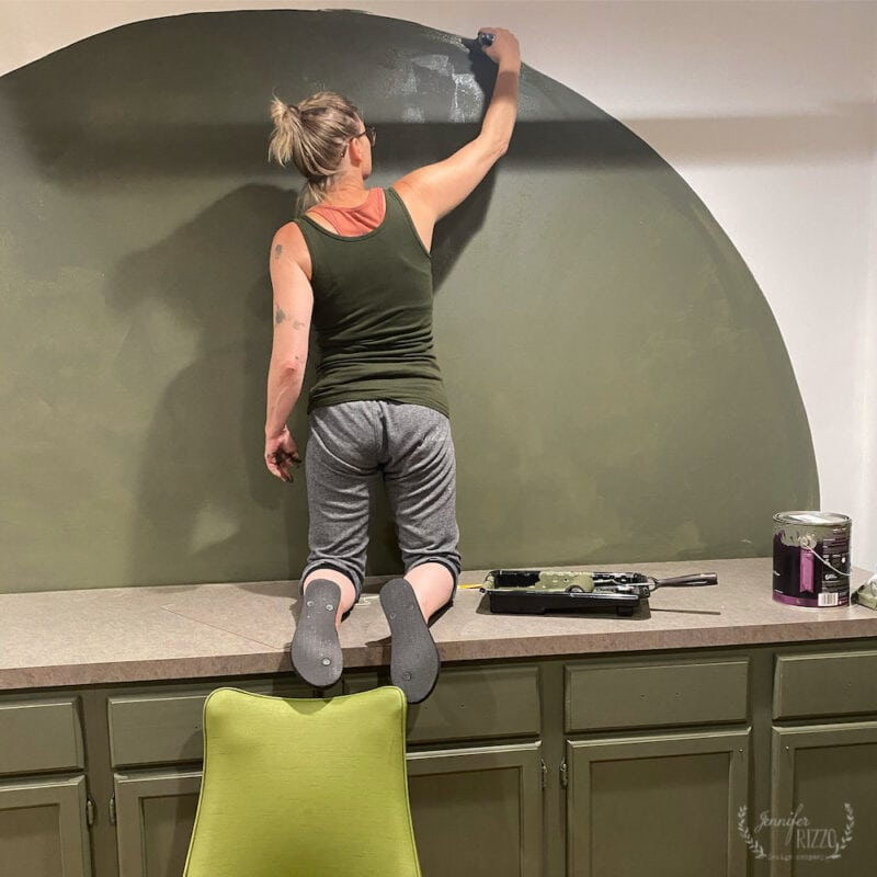 Jennifer Rizzo painting an arch wall