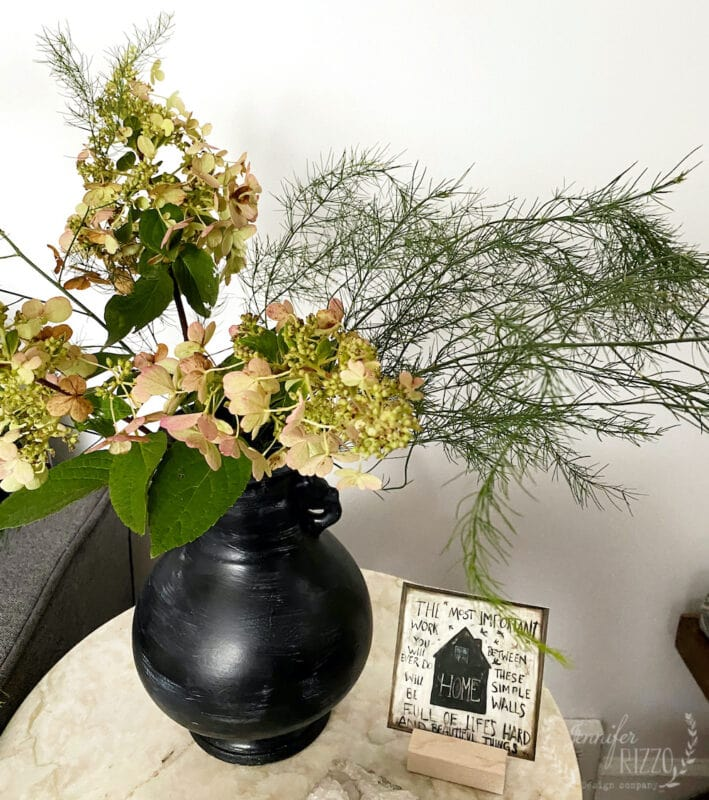 Hydrangeas and asparagus arrangement in a mud washed vase