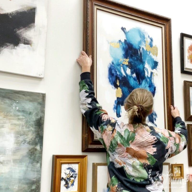 Jennifer Rizzo hanging art at Warehouse 55