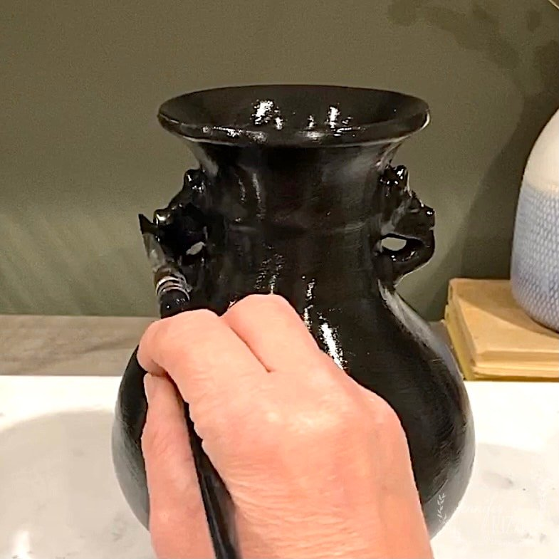 Completely base coat your vase in black paint