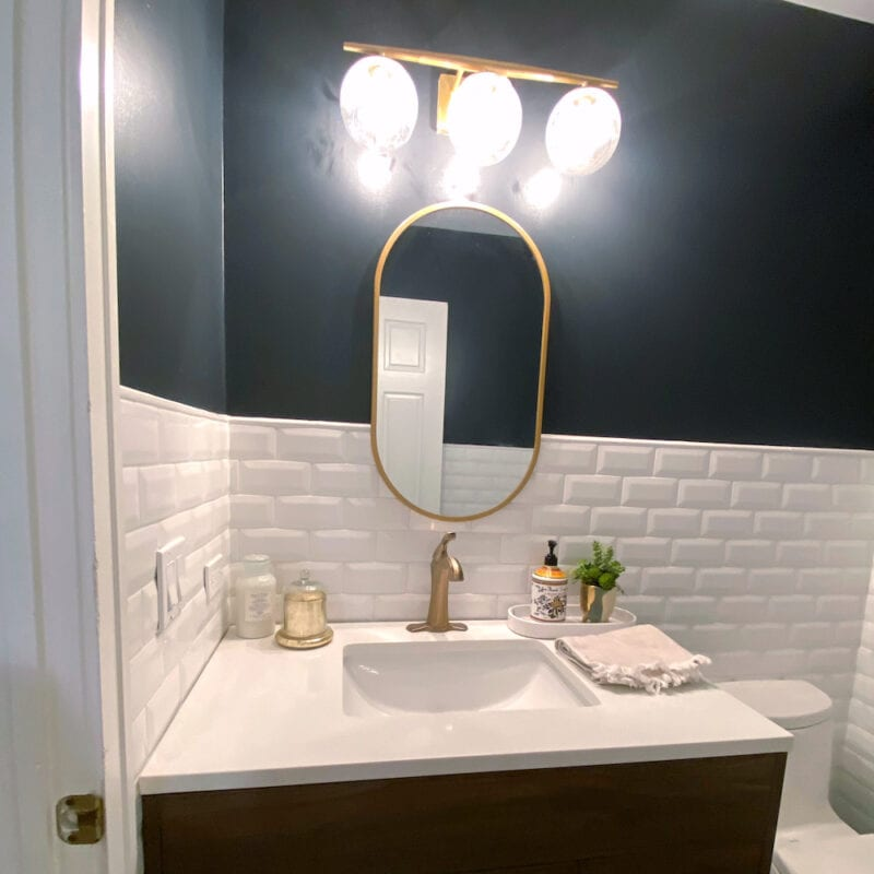 Oval mirror and wood vanity in bathroom renovation