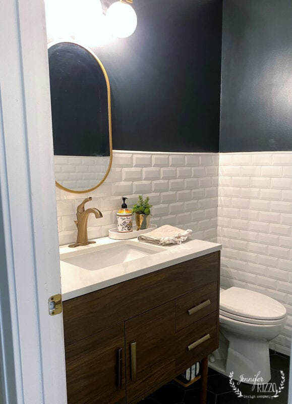 Modern black tile floor and white subway tile bathroom with black paint in a black and white downstairs guest bathroom