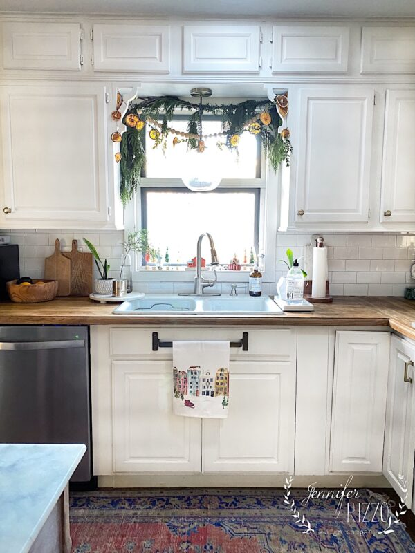 Holiday kitchen window decorated with orange slice garland and greenery