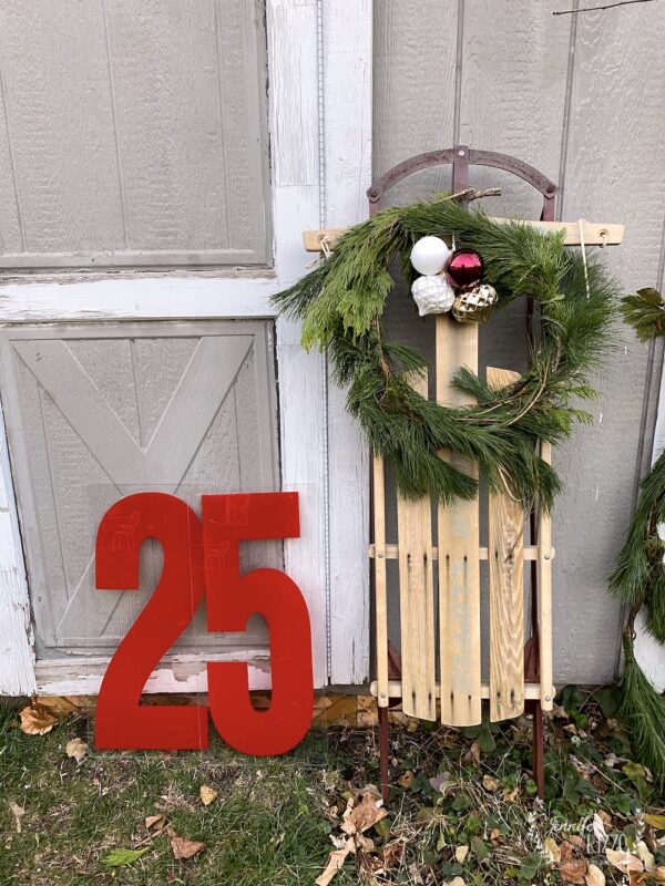 Sled and vintage numbers next to a she shed