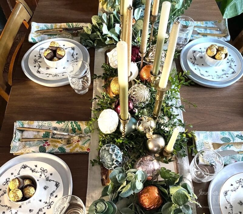 View of a n MCM indpired vintage tablescape with candles greenery and vintage plates