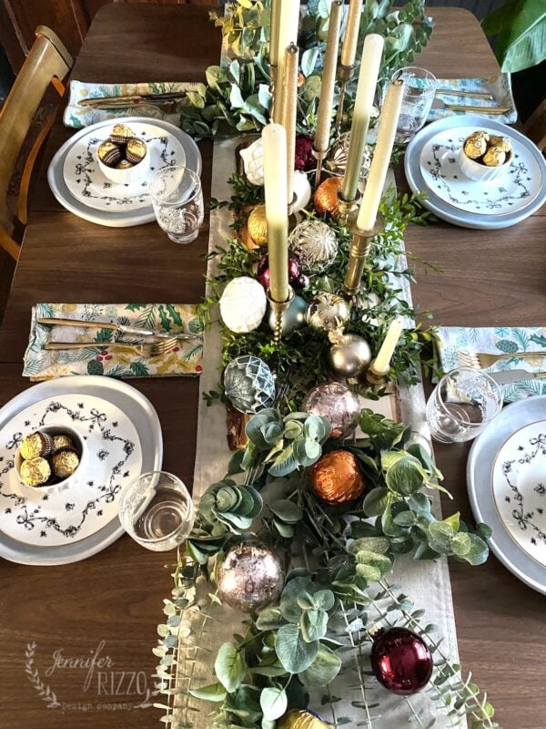 View of tablescape with candles and greenery layered withornaments