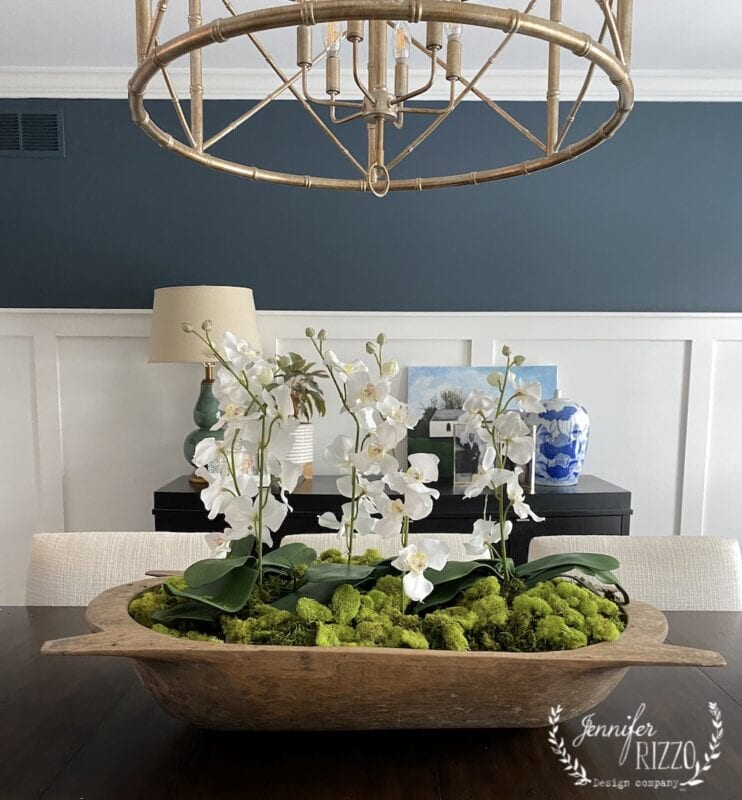 Dining room with vintage wood dough bowl and faux orchids and moss