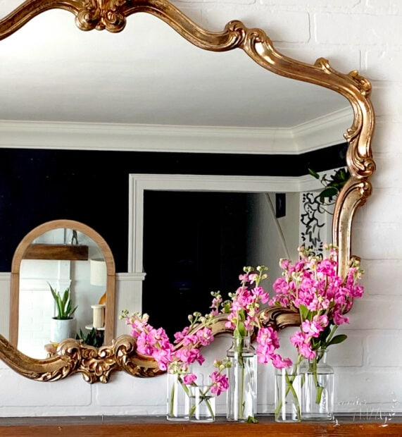 Gold mirror and bottles on mantel for spring