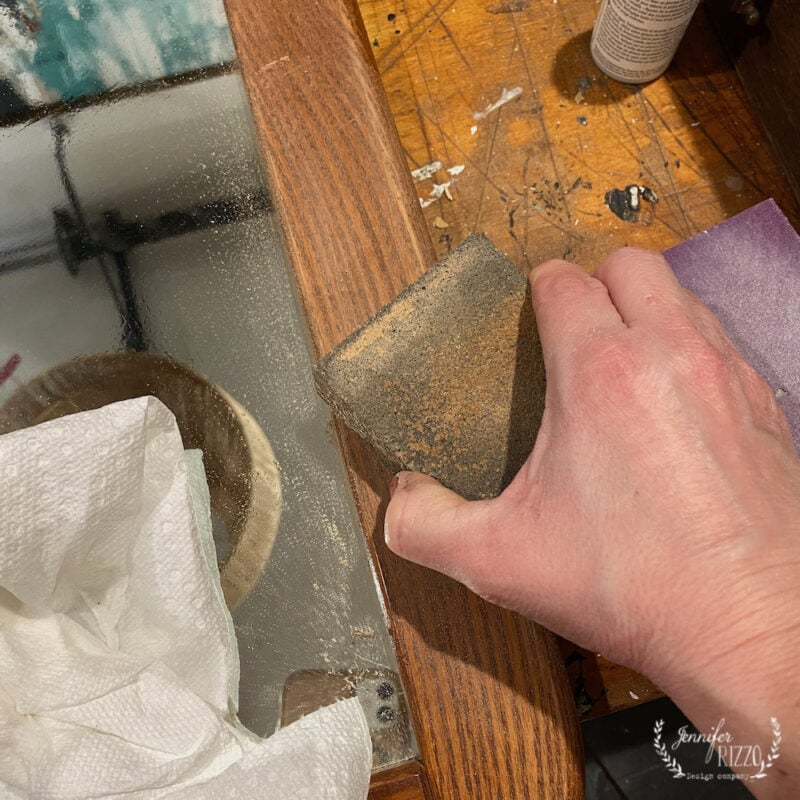 Sanding a wood mirror