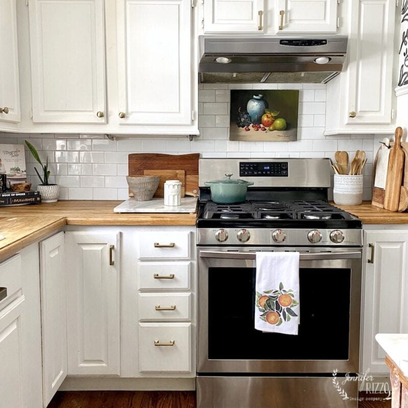 White kitchen cabinets oil painting over stove for early spring kitchen decor