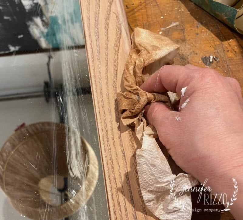 cleaning sanded wood frame with a tack cloth