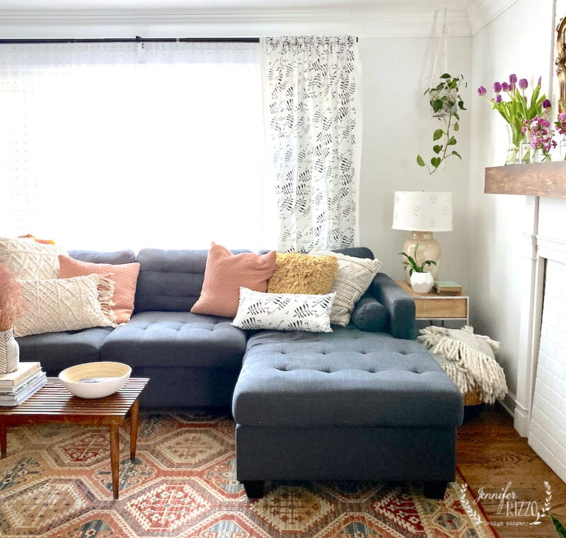 Casual boho living room with colorful rug and gray couch