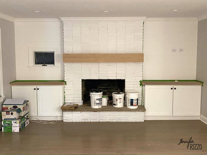Fireplace painted white with built in cabinets on each side