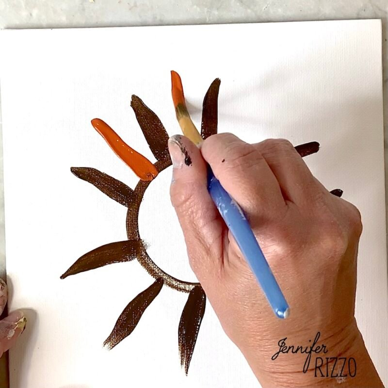Layer burnt orange paint to create more sunflower petals