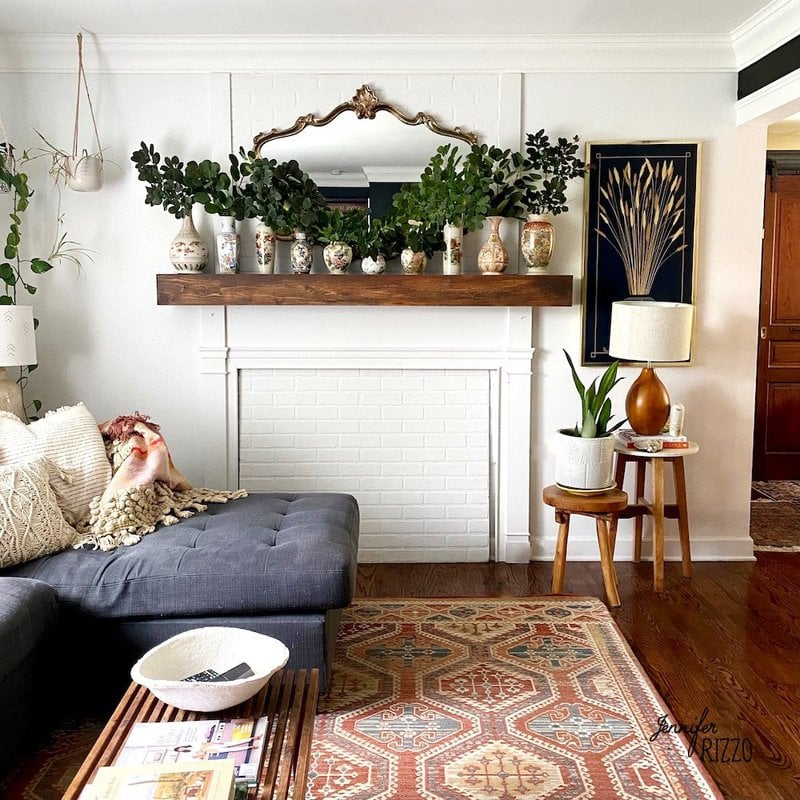 Living room with smoke bush clippings in vintage vases on mantel