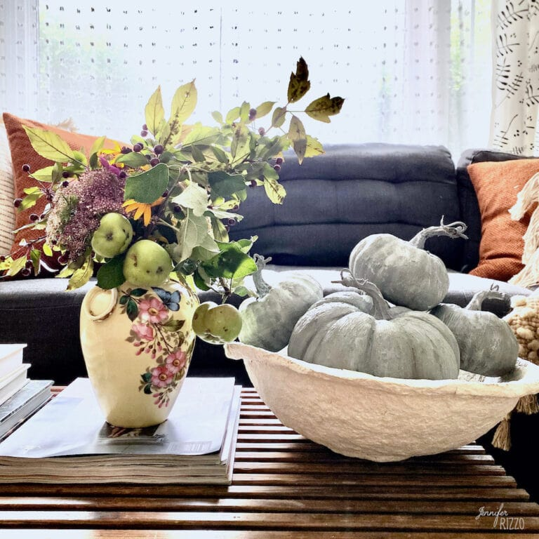 Terra Cotta painted baking soda paint pumpkins with a vase of flowers and apples in a paper mache bowl