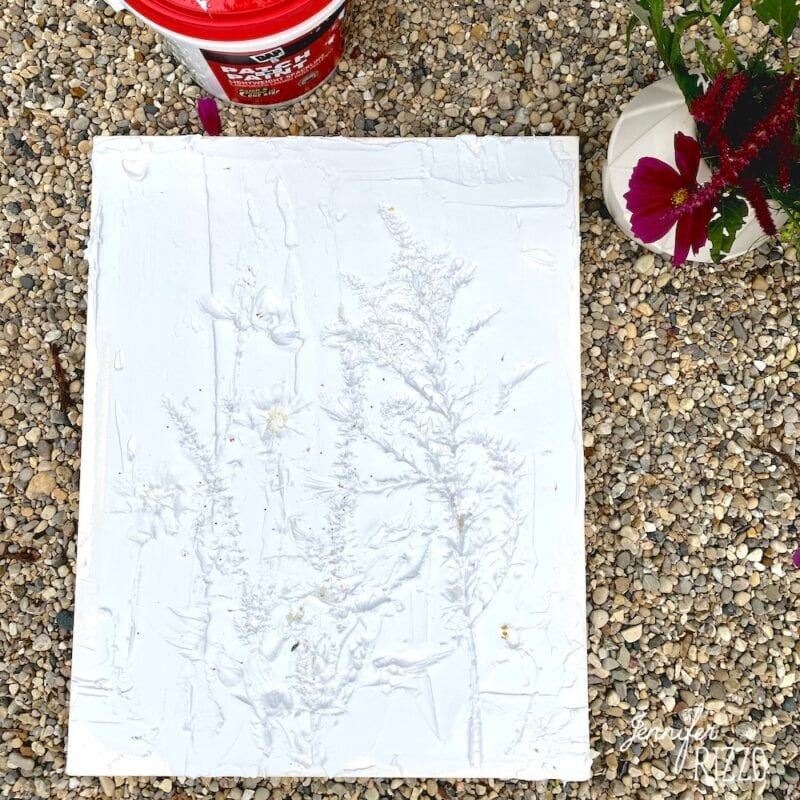 Art made from pressing flowers into spackle