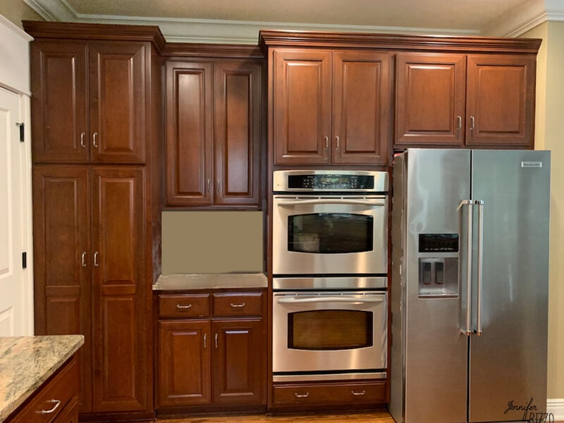 Dark kitchen cabinet with oven and fridge before cabinet refacing