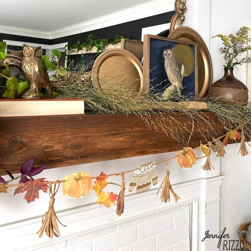 sweater and pumpkin fall banner with DIY raffia tassels on a fall mantel wkith owls and foraged grasses