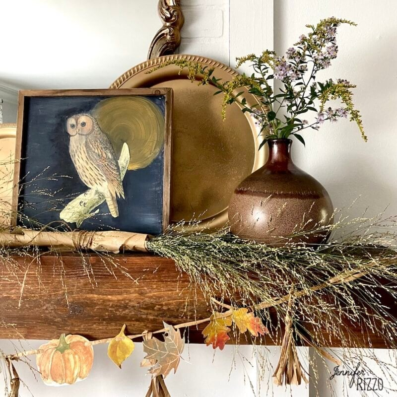 Framed owl prints and wiildflowers and gold tray on mantel