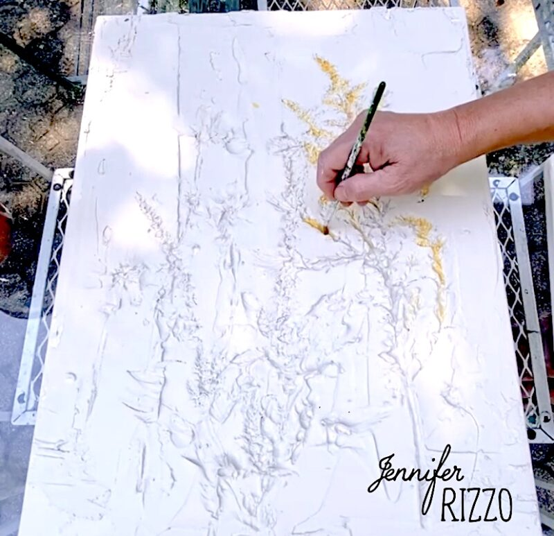 Painting the inside of the flower impressions when making a DIY abstract floral impression art with spackling paste