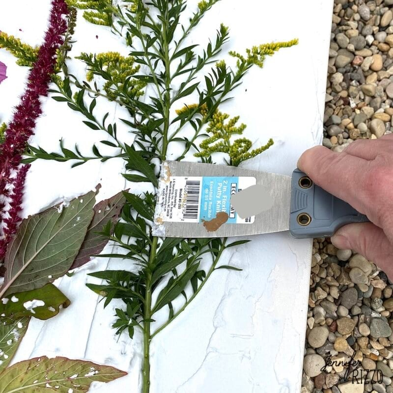 Press flower stems into spackle or drywall compound