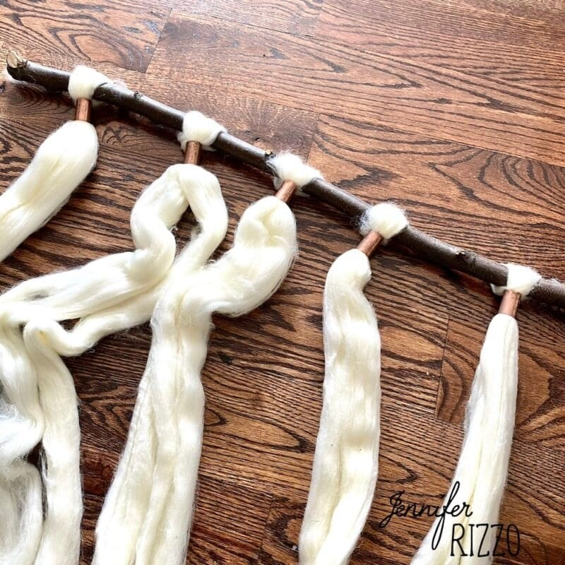 Wool roving yarn on a branch with copper couplings